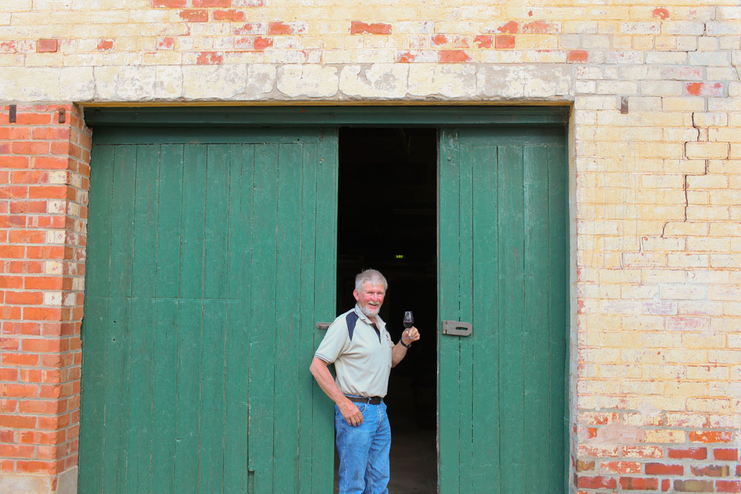 Chateau Mildura winemaker Lance Milne green shed doors with glass of wine
