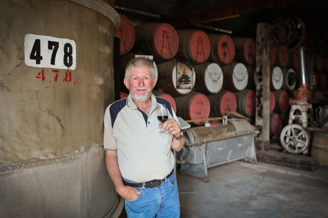 Chateau Mildura winemaker Lance Milne in winery shed with glass of wine